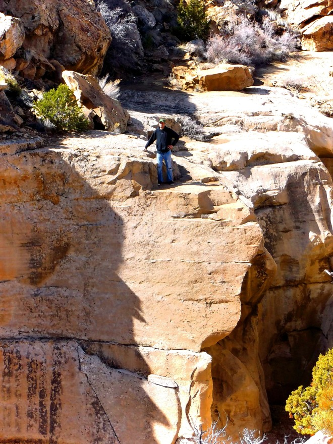 Jered, the fire maker, precariously perched above a desert chasm