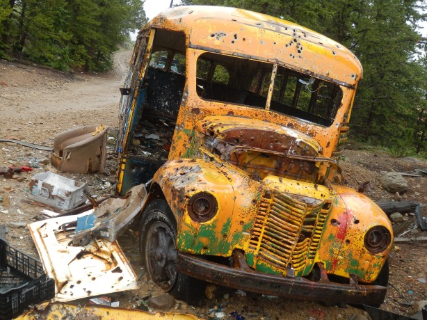 Old school bus shot full of holes near Stumptown above Leadville, surrounded by modern day garbage- an armchair, plastic milk crates, assorted TV guts and electronics...disgusting!